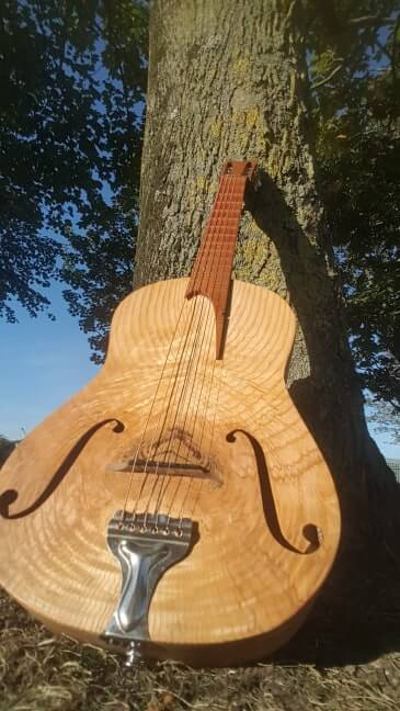 Cork-Guitars - handmade instrument in front of a tree