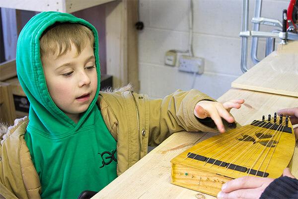 Cork Guitars - Boy plays handmade instrument